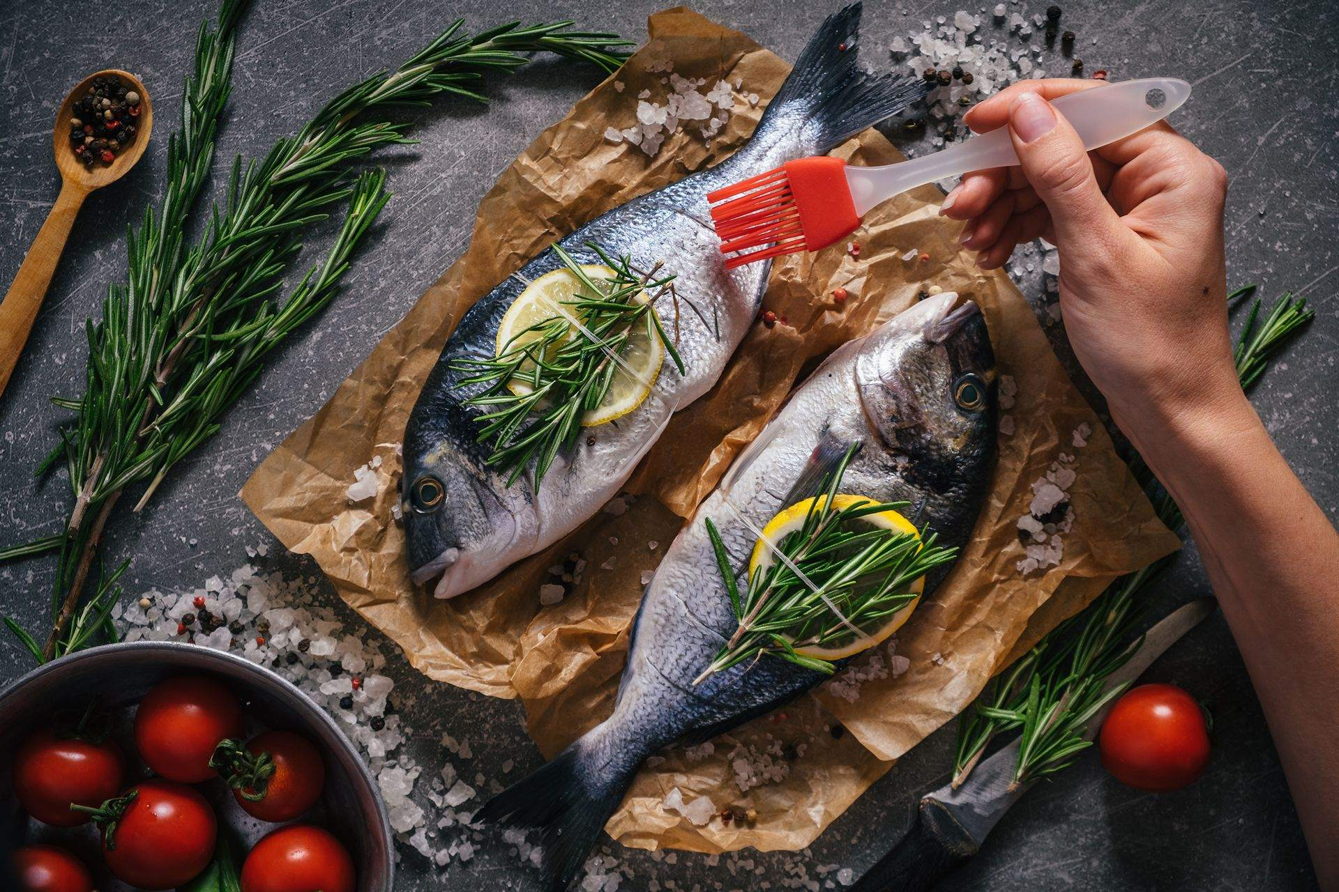 Preparing seafood fish for cooking on grill. Dorado fish with aromatic herbs and vegetables on rustic wooden board and dark background, top view