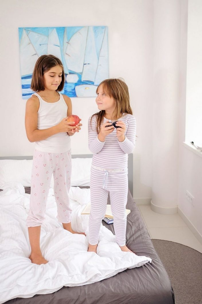 Two young girls standing on the bed in early morning and waiting for mother.