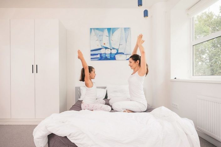 Young mother and daughter gets up and doing morning yoga exercises in bed. Healthy lifestyle concept