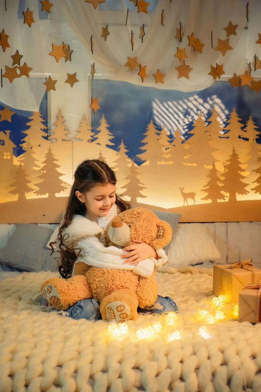 Cute little girl playing with teddy bear bed in room decorated for New Year. Winter weekends. Cozy scene. Holiday atmosphere.