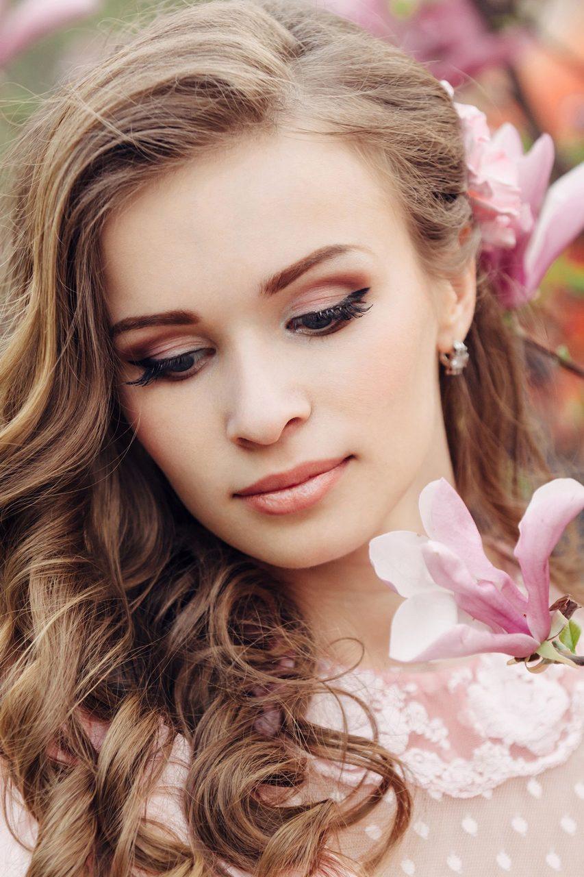 Sensual woman portrait in the blooming magnolia garden