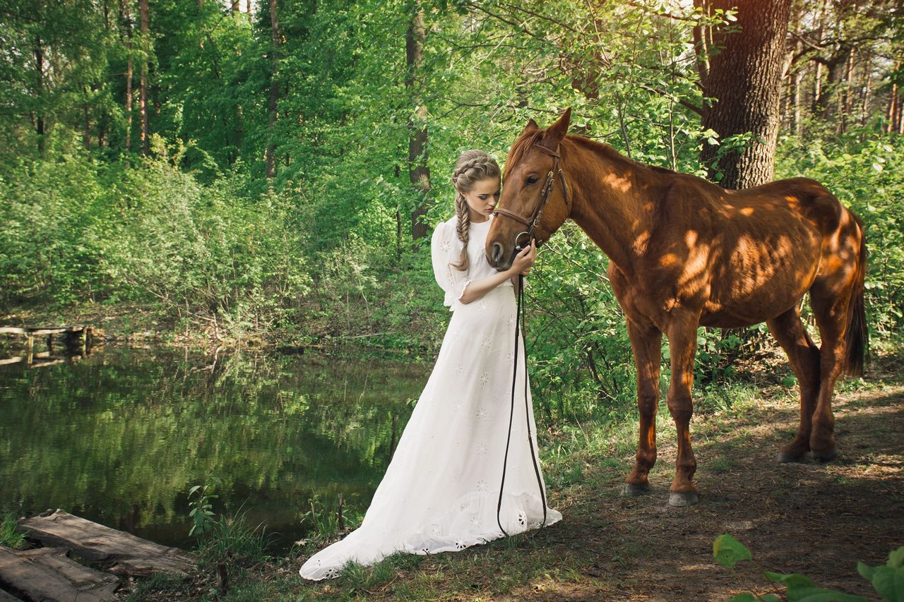 Woman standing with horse near forest and touching to face