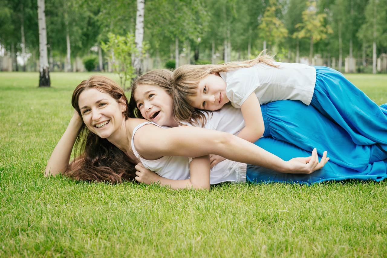 Mother with kids having fun playing outdoors. Family has the same clothes. Happy children lie on mom's back