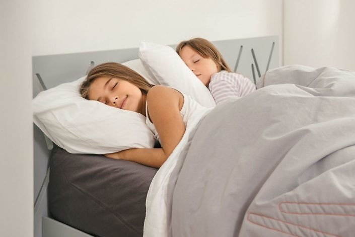 Sweet dreams of two young girls in the morning at home. Top view of bed in the room