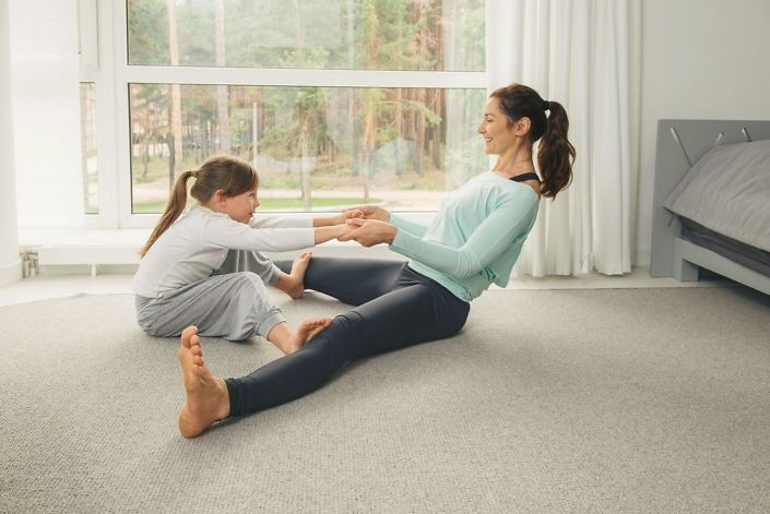 Mother and daughter making gymnastics and stretching at home. Family healthy lifestyle concept.