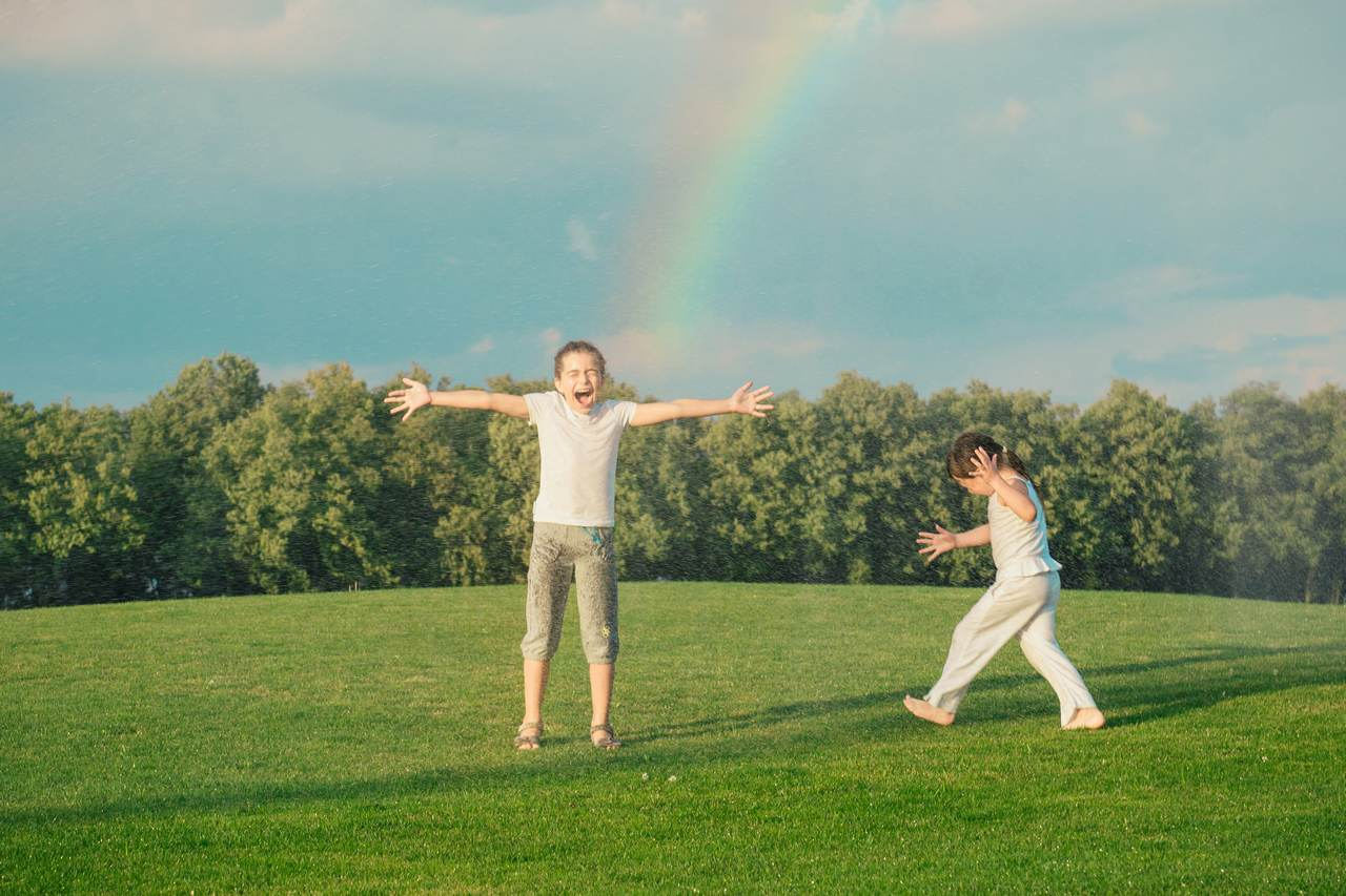 Happy children playing under rainbow from water sprinkler in the park. Two kids with hands up on sunshine through splashes outdoor.
