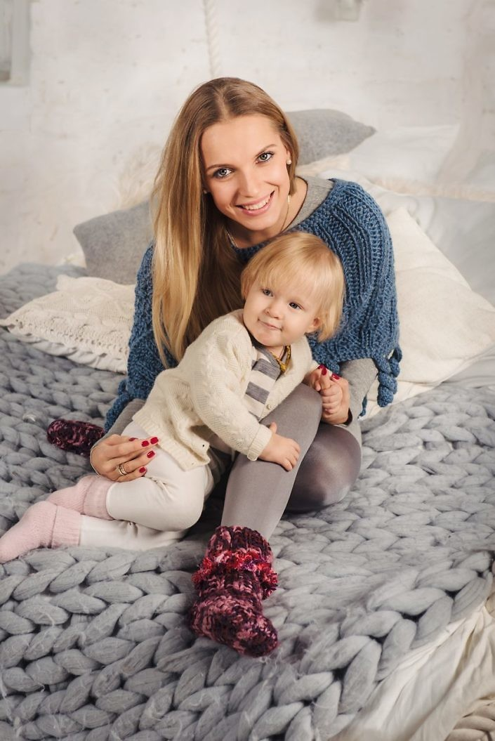 Happy blonde mother embrace her little baby daughter on the big bed in winter. Family at cozy home.