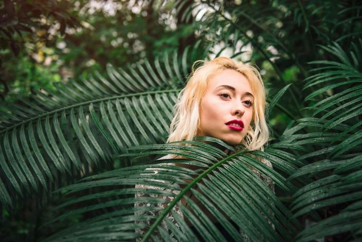 Closeup portrait of sensual female fashion model with damp blond hair and red lips standing behind the palm branch, covered in it. Having a dreamy look, at the botanical garden.